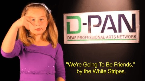 "Image description: photograph of young girl with blond hair and light skin, She is using American Sign Language. In the background a large white rectangular sign reads D-PAN, Deaf Professional Arts Network. Closed Captioning in Yellow at bottom of image reads"" We're Going To Be Friends , "" by the White Stripes."