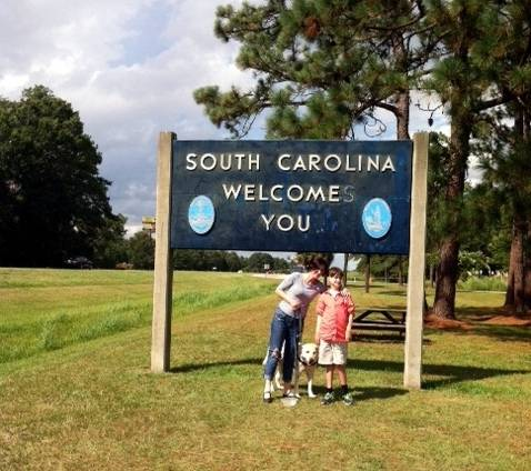 South Carolina Welcomes You road side sign, woman, boy and dog stand underneath