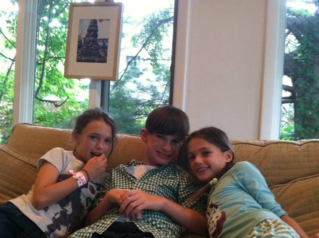 picture of girl, boy and girl sitting on couch smiling