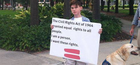 Boy with brown hair and blue and white checked shirt holds sign that reads The Civil Rights Act of 1964 granted equal rights to all people. I am a person. I want these rights.