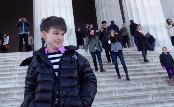 a teenage light skinned boy with freckles, wearing a black jacket, blue and white striped sweater, pink collared shirt is standing in front of large columns and steps that lead to the Lincoln Memorial