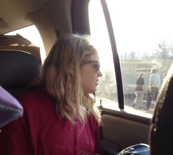 Photograph of Issy Stapleton. Light skinned blonde girl with shoulder length hair looks out a car window. She is wearing sunglasses and a pink tshirt.