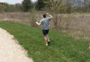 Boy with gray shirt running in grass