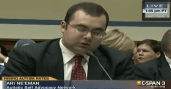 Image description: Photograph of screenshot of C-SPAN a light skinned man with black hair. He is wearing glasses and a dark grey suit, light shirt and maroon tie. Ari Ne'eman Autistic Self Advocacy Network