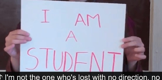 "Image description. Hands holding up a white sign with pink text "" I AM A STUDENT"" Closed captioning text"" I'm not the one who's lost with no direction, no"""