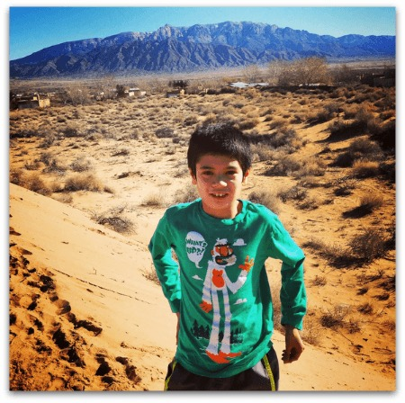Image of young boy with olive skin and black hair smiling. He is standing in the desert.