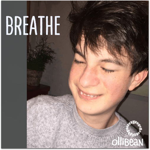 "Image description: Photograph of boy with white skin and brown hair smiling with his eyes closed. ""Breathe"" is in text at top of image and Ollibean Logo is at the bottom."