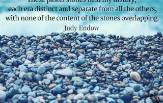 "Photograph of stones on a beach. Text reads "" hese pastel stones held my history, each era distinct and separate from all the others, with none of the content of the stones overlapping. Judy Endow on Ollibean."